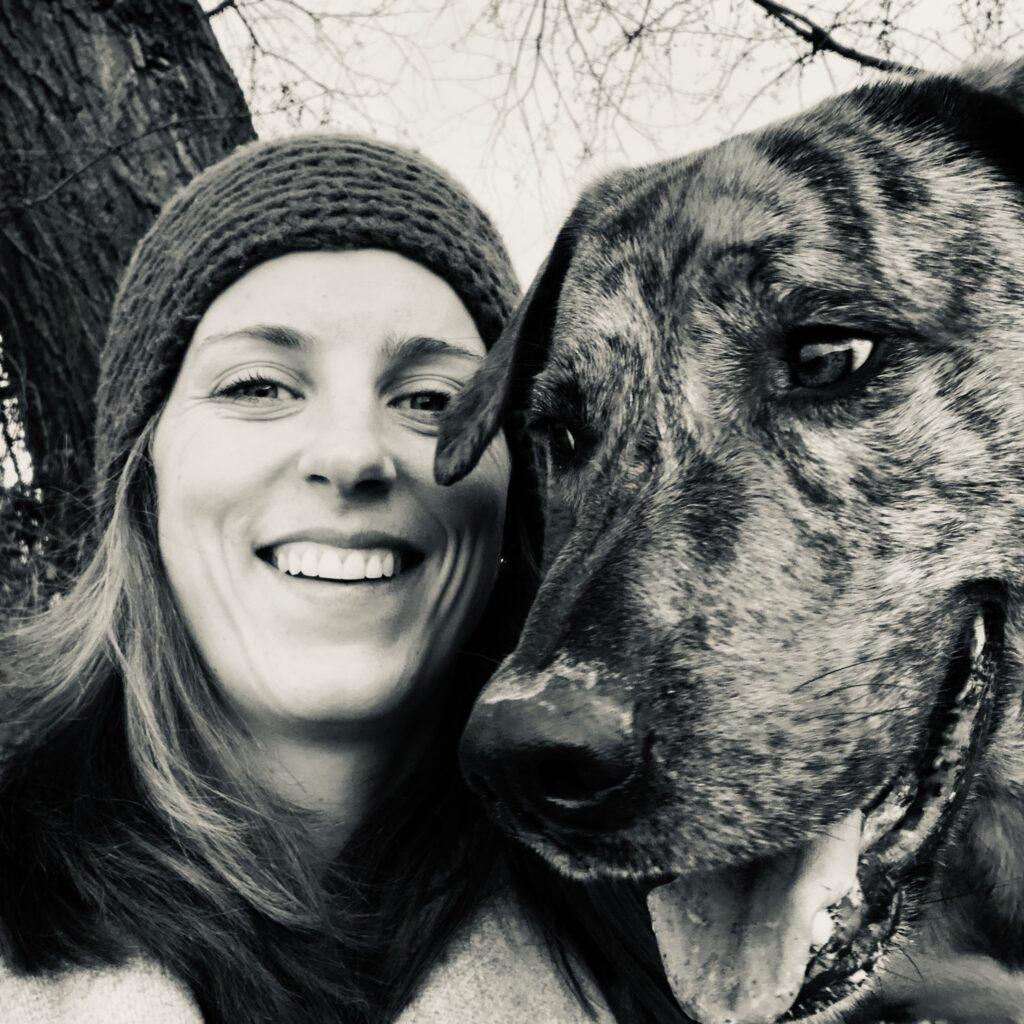 Frau lächelt in die Kamera, neben ihr ist der Kopf eines Hundes zu sehen