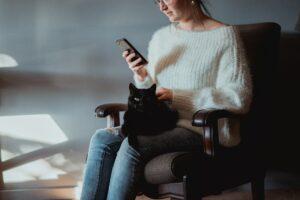 Frau sitz auf einem Sessel und schaut auf Ihr Smartphone auf ihrem Schoß liegt eine Katze, die von ihr gestreichelt wird