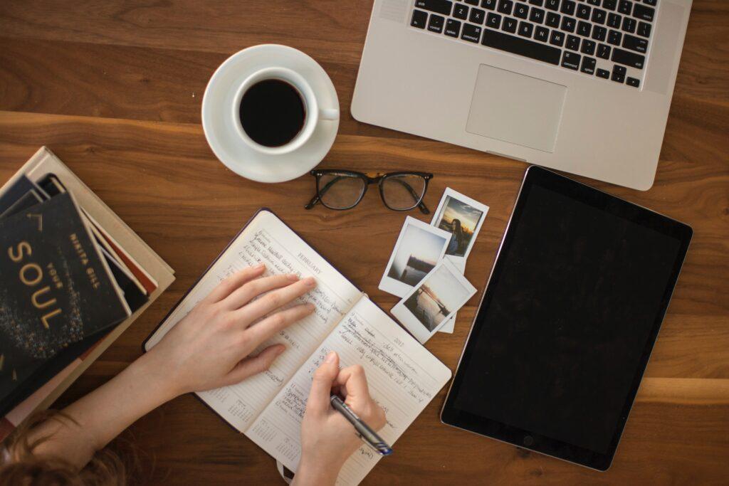 Aufsicht auf einen Tisch mit Arbeitsmaterialien wie Laptop Tablet Notizbuch und einer Tasse Kaffee, eine weibliche Hand schreibt etwas in einen Kalender