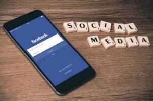 Smartphone mit Facebook App , daneben steht SOCIAL MEDIA Plattformen